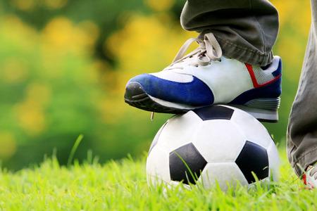tread: human foot tread on football in garden Stock Photo
