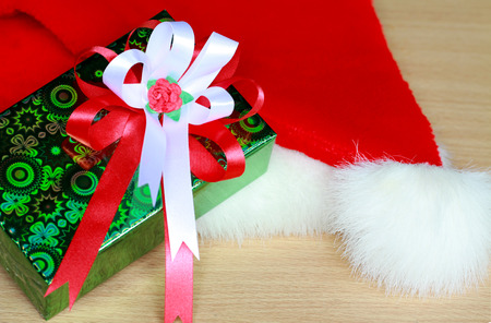 ribbin: green gift box with red and white ribbin on red Santa Claus hat for Christmas