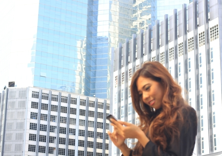 promptly: Portrait of Asian business woman on black dress use moblie with tower background
