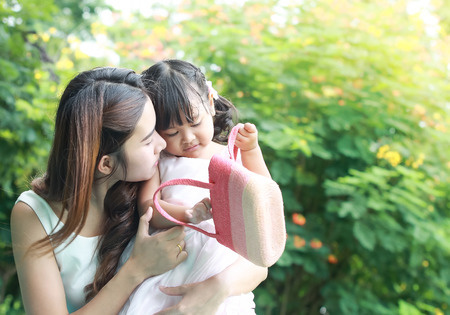 daugther: close up portrait of Asian mother take care young daugther in garden