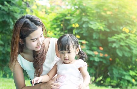 take care: close up portrait of Asian mother take care young daugther in garden