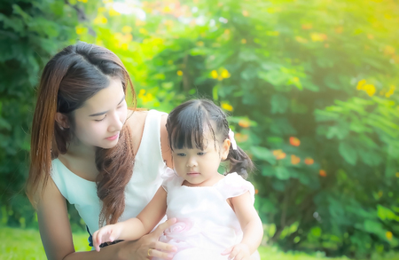 take care: soft focus , close up portrait of Asian mother take care young daugther in garden