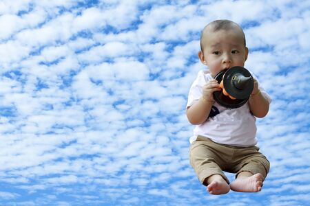 altocumulus: Close up portrait of Asian boy hold pumpkin doll in hand with  Altocumulus cloudy  background Stock Photo