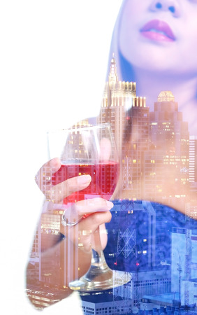 townscape: double exposure and de-focused , woman hand in blue dress holding red wine in wineglass with midnight townscape background