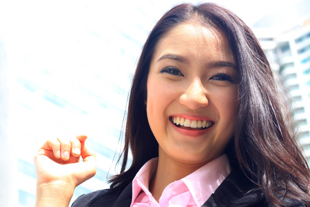 close up portrait of Asian youth business woman look brilliant and success on black suite