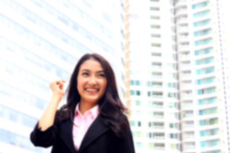 suite: de-focused ,  portrait of Asian youth business woman look brilliant and success on black suite Stock Photo