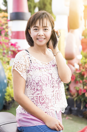 alling: middle age , attractive mature attractive mature Asian woman phoning at home in garden Stock Photo