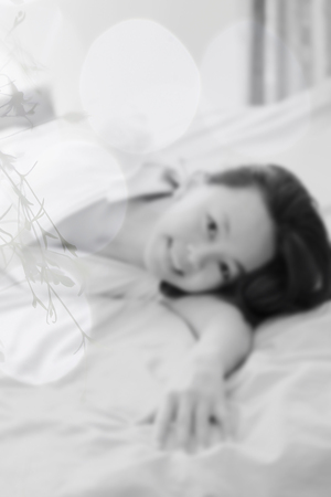 lay down: de-focused , Asian woman on white shirt  lay down on white bed and smile look happy and relax and her eye wtih love , Photo in black and white , double exposure with bokeh light and silhouette of branch