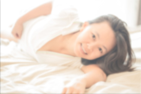 lay down: de-focused , portrait of Asian woman on white shirt  lay down on white bed and smile look happy and relax and her eye with love Stock Photo