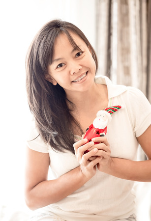 joyfully: close up smile asian woman in white clothes holding toy of Santa in hand , vintage tone