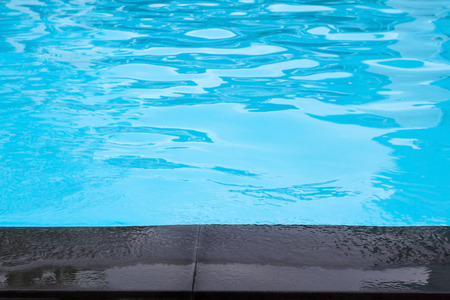Close up edge of  black cement floor near swimming pool with moving blue water Stock Photo
