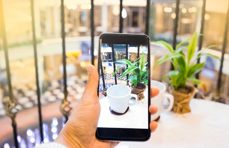 Taking photo of empty white cup with mobile phone Stock Photo