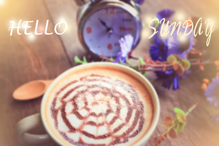 sweet dreamy and de-focused , HELLO SUNDAY word on vintage background coffee latte art and watch on wooden table