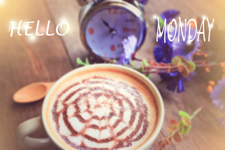 sweet dreamy and de-focused , HELLO MONDAY word on vintage background coffee latte art and watch on wooden table