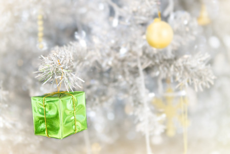 green gift box decorated on white Christmas tree
