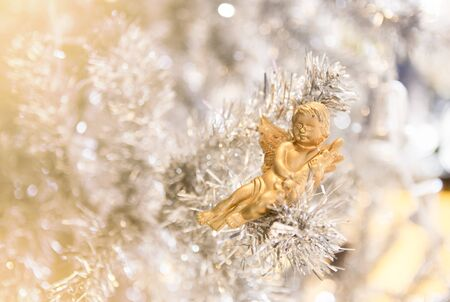 cute golden doll decorated on white Christmas tree Stock Photo