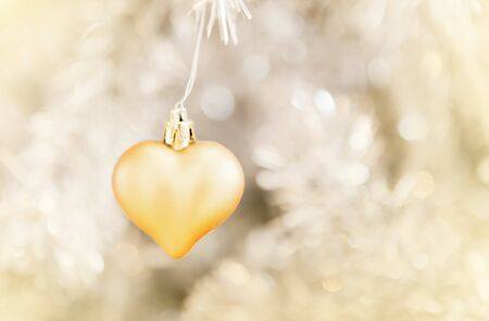 little golden heart decorated on white Christmas tree
