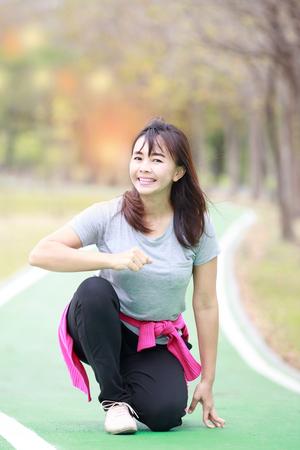 Asian woman preparing to run in garden , soft focus Stock Photo
