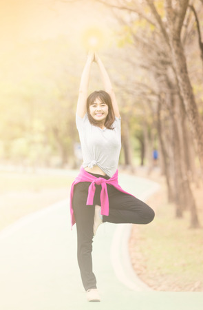 sweet dreamy and de-focused , Attractive woman practices standing in Vrksasana Posture at nature garden , Relax and active lifestyle concept ,  soft focus in vintage tone