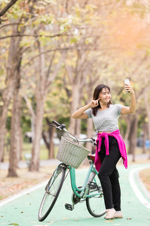 sweet dreamy and soft focus , Attractive woman selfie with phone after ride bicycle in countryside road  , lifestyle concept ,  vintage tone Stock Photo
