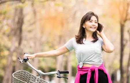 Attractive woman taking with phone while ride bicycle in countryside road  , lifestyle concept ,  vintage tone