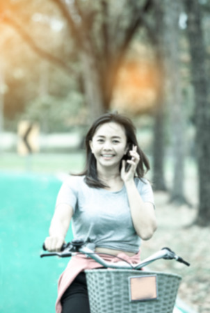 de-focused , Attractive woman taking with phone while ride bicycle in countryside road  , lifestyle concept , cool tone