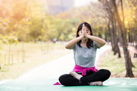 Beautiful mature woman posing in sit meditation at nature garden. Relax and active lifestyle concept ,  soft focus in vintage tone