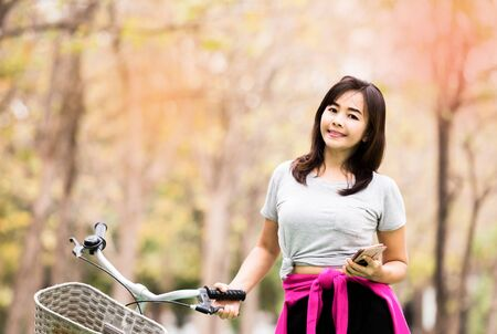 Attractive woman posing with phone and bicycle in countryside road  , lifestyle concept ,  vintage tone Stock Photo