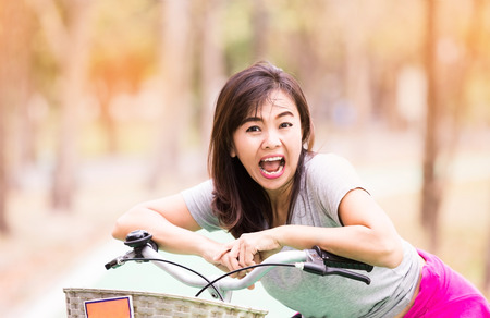 Attractive healthy mature woman ride bicycle and expression of surprise in countryside , lifestyle concept ,  vintage tone Stock Photo
