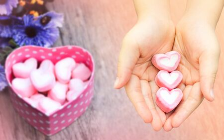 Valentine day concept , close up pink Marshmallow preserve on hand on blurred background of pink Marshmallows in pink heart  box on wooden table , vintage tone
