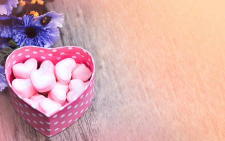 Valentine day concept , pink Marshmallows in pink heart  box on wooden table , vintage tone