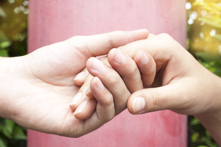 close up human hands holding together on red background , Help and support concept Stock Photo