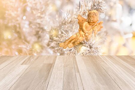 cute golden doll decorated on white Christmas tree and background of ivory panel texture