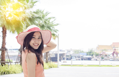Young beautiful Asian woman wearing pink straw hat with expression of happy in garden , vintage tone