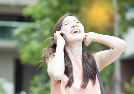 portrait of beautiful Asian woman laugh while using smartphone in garden Stock Photo