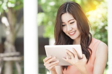 portrait of beautiful Asian woman use tablet in garden