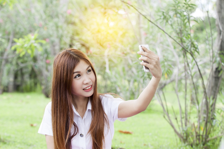 beautiful young woman holding her mobile phone and taking selfie on the trees background