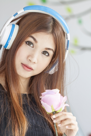 Portrait of a young beautiful woman listening to music with pink rose Stock Photo
