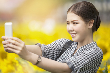 Young happy Asian woman smiling while taking selfie picture with mobile phone in sunflowers field
