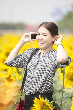 Young happy Asian woman smiling while using mobile phone in sunflowers field Stock Photo
