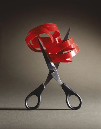 Scissors cut a red ribbon with a bow on ark background.