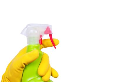 Hand in yellow glove with green sprayer photo