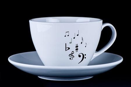 White mug with black musical notes  black background photo