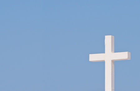 White Christian cross on blue sky background