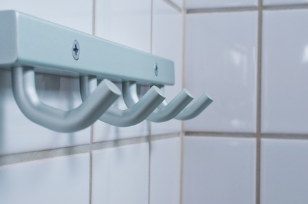 Brushed metal silver towel hanger on rest room wall photo