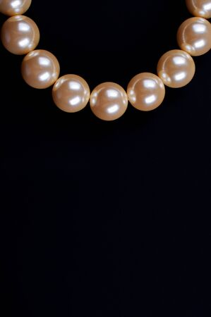 Beige necklace on a black background close up photo