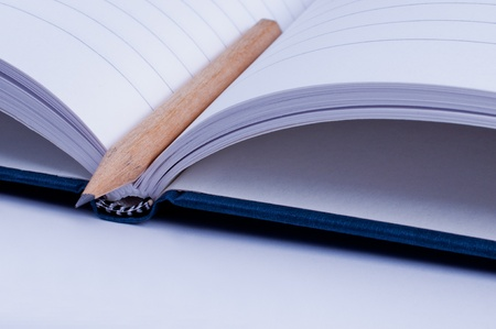 Open blue notebook with pencil  close up photo