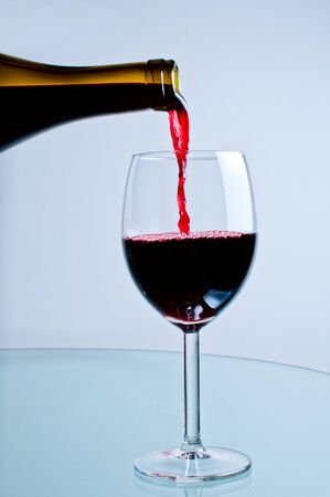 Red wine pouring from bottle into wine glass photo