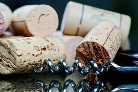 Corkscrew and corks on a glass table close up