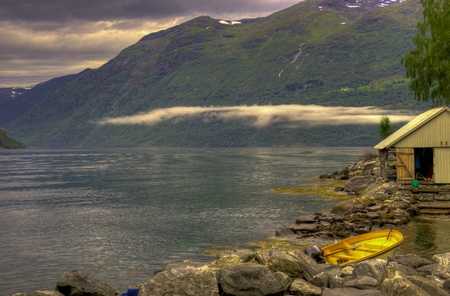 Geiranger fjord HDR yellow boat low clouds photo